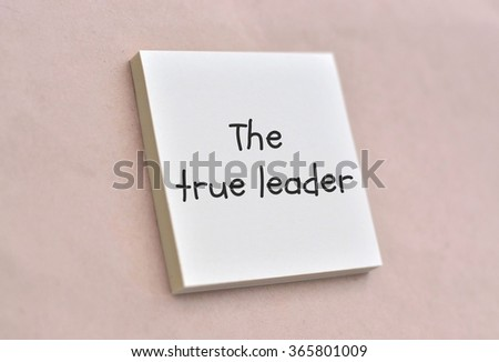 Text the true leader on the short note texture background - stock photo