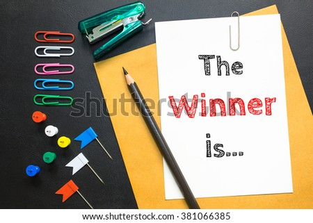 Text The winner is on white paper / business concept