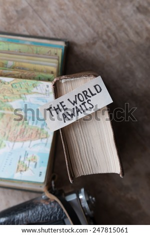 """text """"The World Awaits"""" and book, travel, tour,tourism concept - stock photo"""