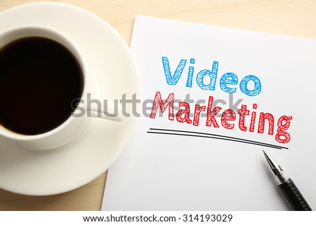 Text Video marketing written on the white paper with pen and a cup of coffee aside. - stock photo
