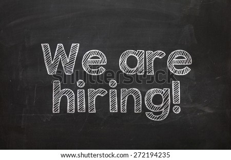 Text We are hiring handwritten with white chalk on a blackboard - stock photo