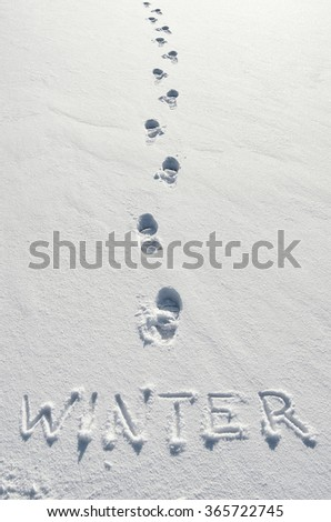 Text WINTER hand written on snow background and footsteps marks. Vertical postcard template. - stock photo