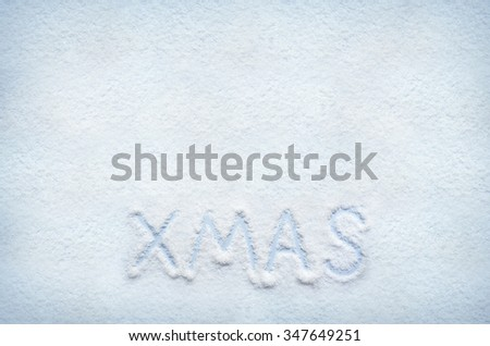 Text XMAS written on snow. Horizontal postcard with space for lettering or copy. - stock photo
