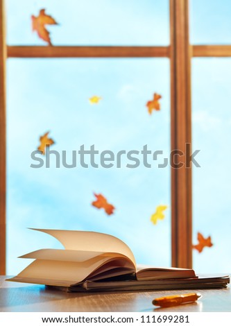 Textbooks on window background with maple leaves - stock photo