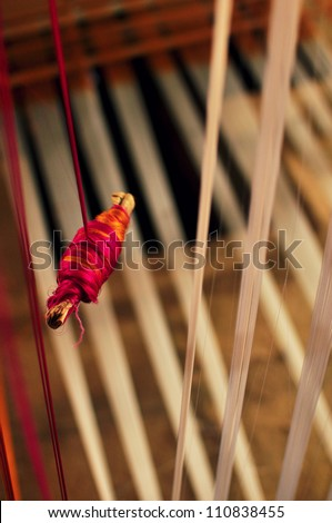 Textile and hand loom background with spool and colorful threads - stock photo