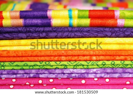Textile background.  Macro of folded cotton fabrics in bright colors. Swatches in coordinated colors for quilting, crafts, or home decor sewing projects.  - stock photo