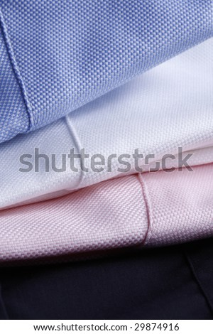 textile background - white, pink and light blue business shirts stacked - plenty of copy-space