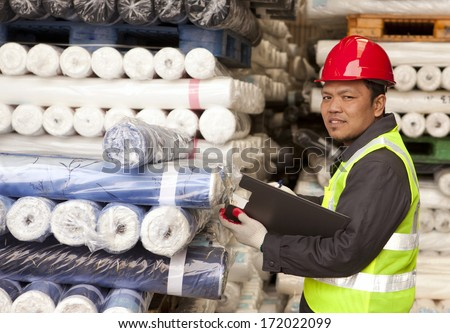Textile factory foreman checking raw material fabrics in warehouse - stock photo