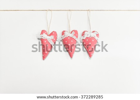 Textile handmade hearts on white wall. Beautiful holiday background - stock photo