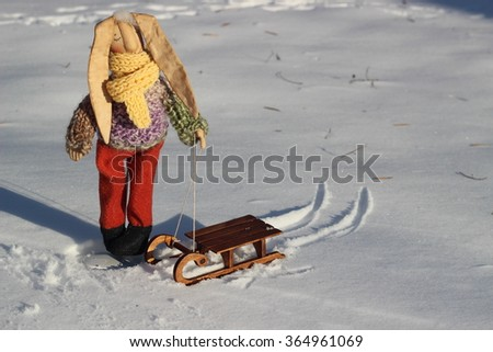 Textile handmade homemade toy fabric rabbit in orange pants and a knit sweater and beige scarf with little brown wooden sled on snow
