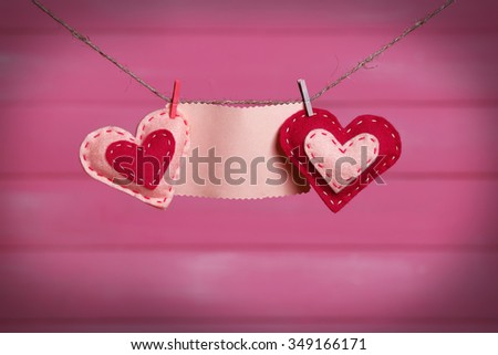 Textile hearts and empty sheet hanging on cord against pink wooden background - stock photo