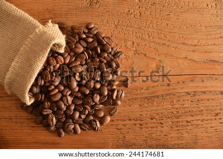 Textile natural material sack of coffee beans on old retro vintage aged yellow brown wooden board kitchen table background Empty texture space for inscription  - stock photo