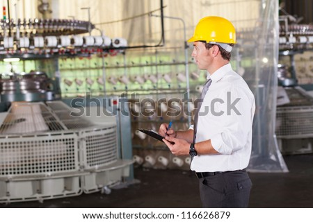 textile production manager working inside factory - stock photo