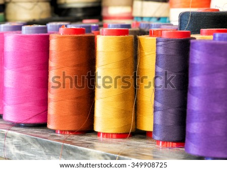 Textile Still Life - Close Up of Industrial Size Spools of Cotton Thread in Vibrant Colors of Pink, Orange, Yellow and Purple - stock photo