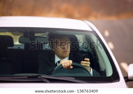 Texting and driving a car - stock photo