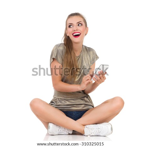 Texting Girl. Smiling young woman sitting on a floor with legs crossed holding telephone and looking away. Full length studio shot isolated on white. - stock photo