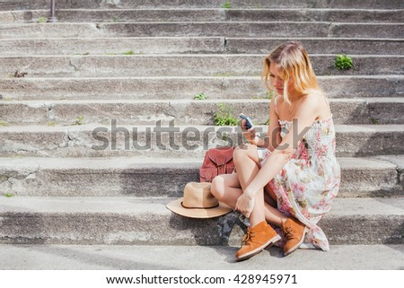 texting on mobile, woman using smartphone app while sitting on the stairs, social network - stock photo