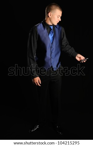 Texting Prom Date. Young man in a black and blue tuxedo looking at his cell phone in front of a black background. - stock photo