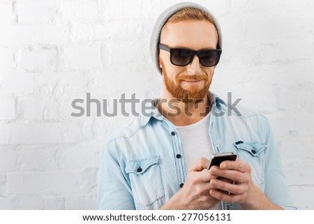 Texting to friend. Handsome young bearded man holding mobile phone and smiling while standing against brick wall - stock photo
