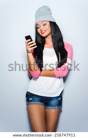 Texting to friend. Happy young African woman in funky clothes typing message to friend while holing smart phone and leaning at the grey background  - stock photo