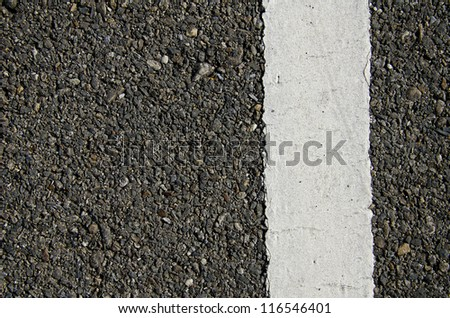 Texture closeup of an asphalt road with painted white line on the side - stock photo