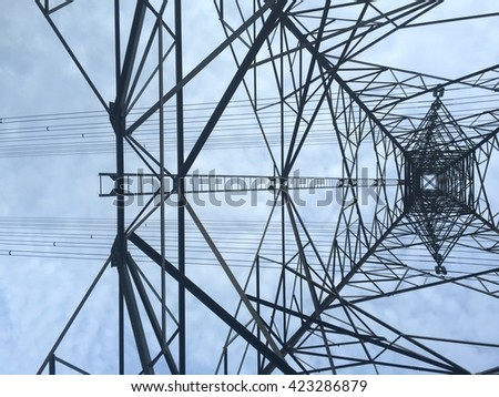 Texture energy pillars. Detail of electricity pylon against blue sky: high voltage electric pillar from below - stock photo