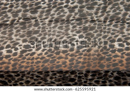 Texture, fabric, background. Beautiful silk scarf with a predatory pattern