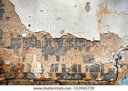 Texture in an abandoned building. Brick, peeling paint, sand