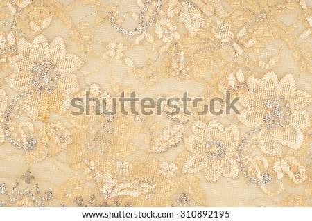 Texture. Lace fabric golden yellow color photos made in the studio. a fine open fabric, typically one of cotton or silk, made by looping, twisting, or knitting thread in patterns  - stock photo