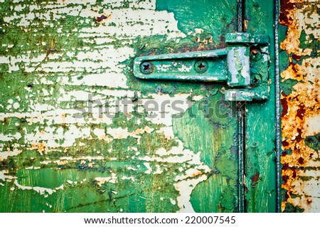 Texture metal door with hinge detail. Rusty door with cracked paint. Green painted door. - stock photo