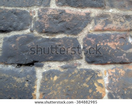 Texture of a rough ancient wall made of stone bricks with irregular shapes - stock photo
