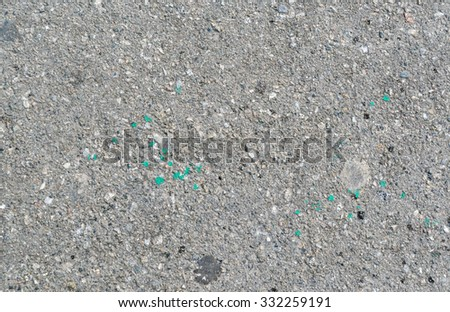Texture of a well used asphalt. There are some oil and paint spots on it. - stock photo