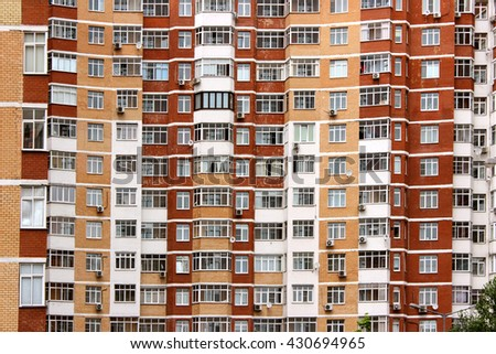 texture of an apartment building with many windows in the afternoon