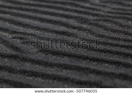Texture of black volcanic sand. Sandy background.