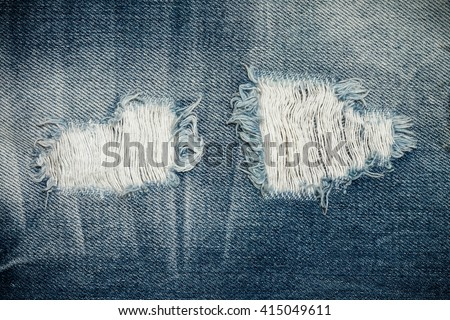 Texture of blue torn denim jean with hole and threads, background