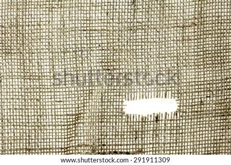 texture of Burlap hessian hole with frayed edges on white background - stock photo