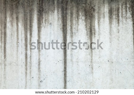 Texture of grey concrete wall with dark water marks running vertically down and many marks and lines