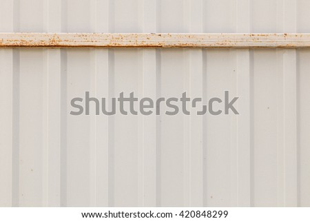 Texture of metal fence picket Profile decking with a rusty rack bar. Internal primed side of a metal picket fence with corrosion of the upper guide bar - stock photo