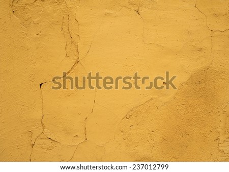 Texture of old rustic wall covered with yellow stucco - stock photo
