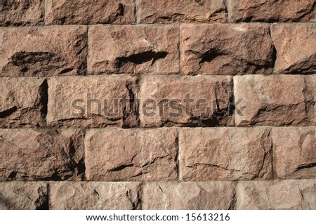Texture of red granite wall in the sunlight