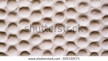 Texture of rose wall plastered in form of honeycombs