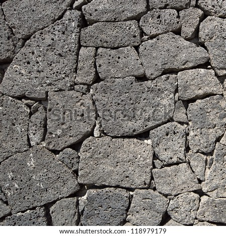 Texture of the black volcanic rock wall from Lanzarote, Canary Islands, Spain. - stock photo