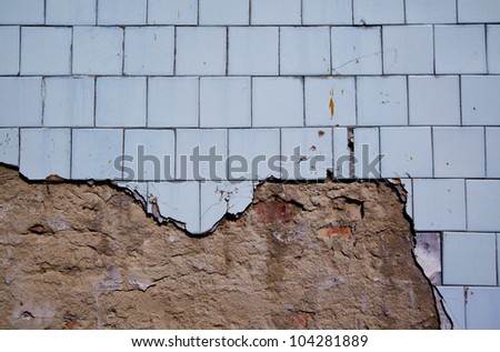 texture of the old tile wall with cracks  broken pavement wall - stock photo