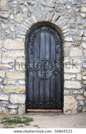 Texture of the old walls and wrought iron doors - stock photo