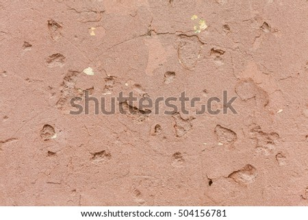 Texture of the wall with holes covered by red stucco