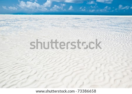texture of the white sand in a beach of Zanzibar during a low tide - stock photo