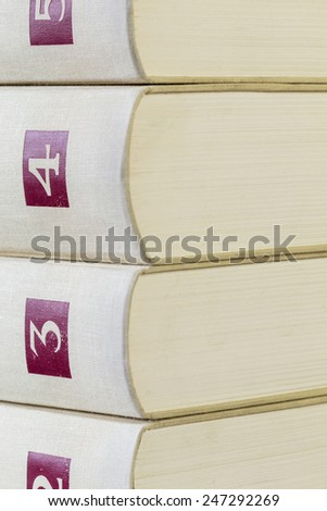 Texture of two leather bound gilt tooled vintage books with decorative patterns on the spines in front of the balance of the set stacked on a table, close up detail - stock photo
