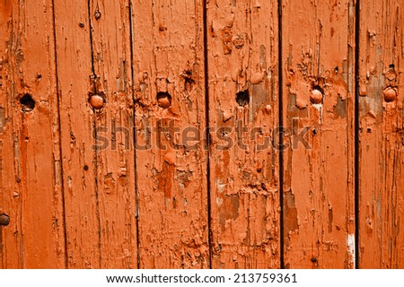 Texture of weathered wooden lining boards with peeling orange paint and rusty nail heads.  - stock photo