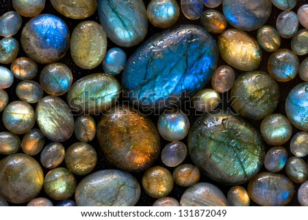 Texture of wet colorful labradorite gem stones. - stock photo