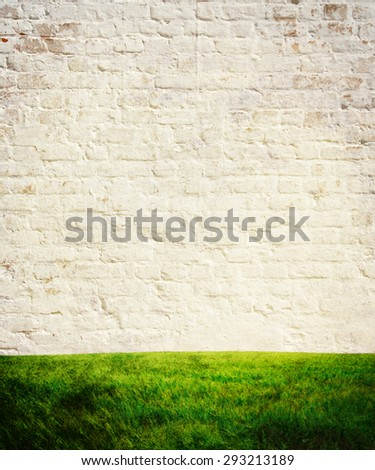texture of white brick wall and green grass - stock photo